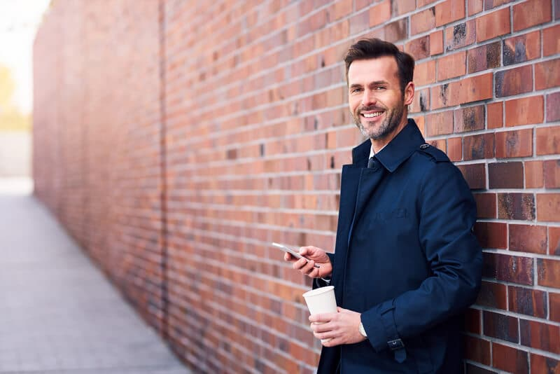 Photo of a man leaning on a brick wall